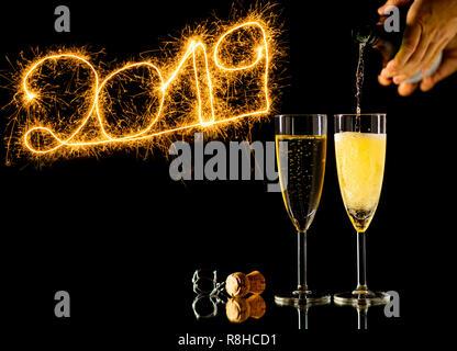 Bonne année deux verres de champagne et de beaux numéros d'or brillant 2019 écrit avec l'éclat d'artifice isolé sur fond noir dans la région de New Y Banque D'Images