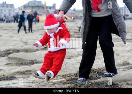 Chase le pudding est une course de 5 km le long de plage de Weymouth habillée en père et la poursuite d'un pudding de Noël et la collecte de fonds pour l'organisme de bienfaisance local la volonté populaire Mackaness Trust. Finnbarr Crédit: Webster/Alamy Live News Banque D'Images