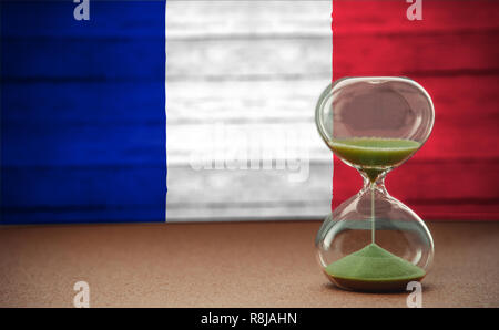 Le sable dans les vases du sablier mesurant le temps qui passe dans un compte à rebours jusqu'à une date limite, sur l'arrière-plan du pavillon France with copy space Banque D'Images