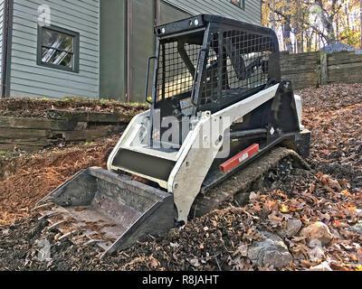 Un petit bulldozer sur le côté d'une maison prêt à se rendre au travail. Banque D'Images