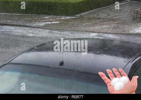 Grande glace grêle billes sur un capot de voiture après une forte tempête de grêle Banque D'Images
