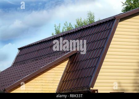 Brown metal roof of rural maison couverte de parement jaune plus de ciel bleu avec des nuages sur sunny day side view Banque D'Images