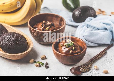 L'avocat de la mousse au chocolat avec les pistaches dans un bol en bois sur un fond blanc. Banque D'Images