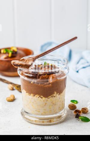 Du jour au lendemain d'avoine avec du lait et la mousse au chocolat dans un verre sur un fond blanc. Banque D'Images