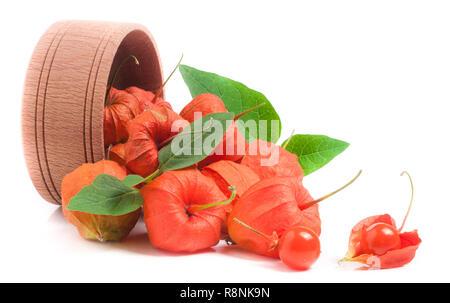 Les tomates avec des feuilles dans la cosse du bol en bois isolé sur fond blanc