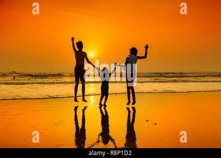 Heureux les jeunes gens qui dansaient sur la plage au coucher de soleil. Banque D'Images