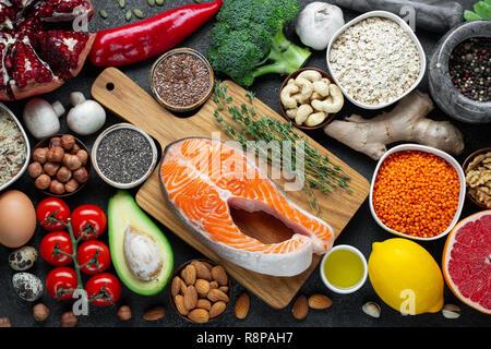 L'alimentation saine manger propre sélection: poissons, fruits, légumes, graines, superfood, céréales, légumes feuilles noires sur fond de béton. Mise à plat Banque D'Images
