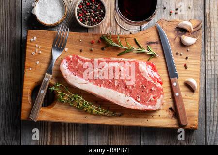 Premier exemple des steaks de boeuf Black Angus avec des épices et du vin rouge sur planche de bois: Contre-filet, faux-filet. Vue d'en haut. Sur une table rustique foncé