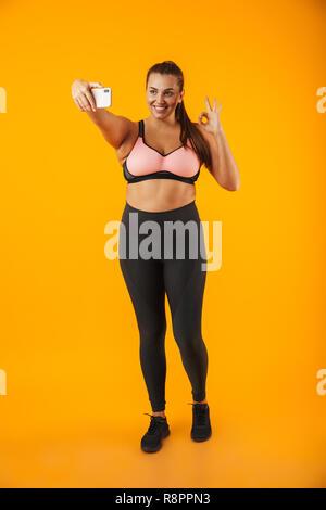 Full Length portrait of smiling woman in chubby soutien-gorge sportif prendre photo selfies sur téléphone mobile sur fond jaune isolé Banque D'Images