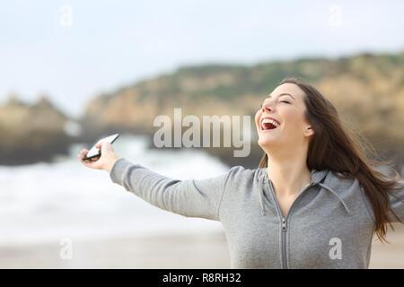 Excited woman holding smart phone étend les bras sur la plage