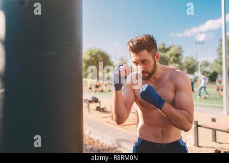 Jeune homme d'entraînement de boxe. Exercice Boxer boxer boxe athlétique. Concept main punch par sac de boxe. Banque D'Images