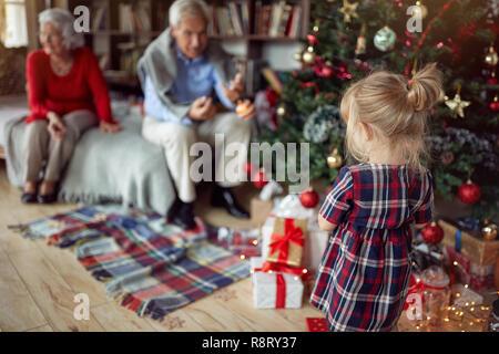 Jolie fille est jouer en face d'un arbre de Noël décoré Banque D'Images
