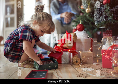 Cute little girl joue en face d'un arbre de Noël décoré Banque D'Images