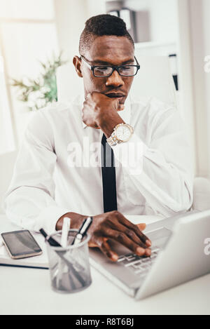 Pensive African businessman est working on laptop in office moderne et de planification que faire ensuite. Banque D'Images