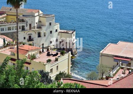 Terrasse méditerranéenne construire des maisons sur des falaises rocheuses le long de la côte accidentée avec de belles vues sur la mer bleue. Banque D'Images