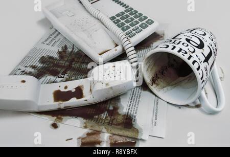 Renversé du café sur l'appareil téléphonique et revues Banque D'Images