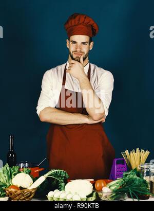 Chef avec visage souriant détient main sur menton sur fond vert sombre. L'homme à chapeau et un tablier cook. Une cuisine traditionnelle et cuisine professionnelle concept. Cook travaille en cuisine près de table avec des légumes et des outils. Banque D'Images