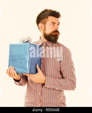 Cadeau bleu enveloppé avec macho et arc blanc. Guy dans la chemise à carreaux est titulaire présent fort. Surprise et cadeau de concept. Homme avec barbe et curieux visage semble côté isolé sur fond blanc. Banque D'Images
