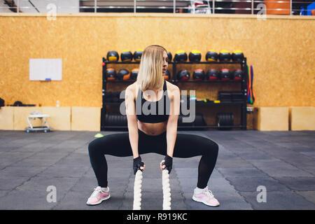 Strong Woman cordes bataille dans la salle de sport. Faire de l'athlète à l'entraînement de corde bataille de sport. Banque D'Images