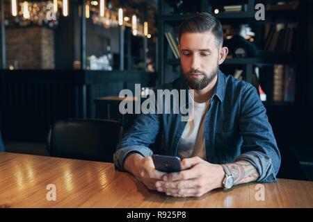 Jeune homme barbu, vêtu d'une chemise en jean, assis à table dans un café et d'utiliser votre smartphone. L'homme à l'aide de gadget. Banque D'Images
