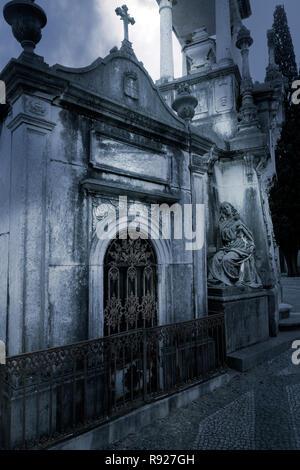 Vieux cimetière européen avec une statue de la mort dans un coin