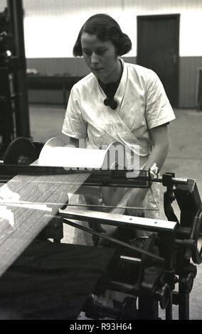 1940, historique, un jeune adulte travailleur féminin dans un manteau blanc l'exploitation d'une machine dans une usine de textile, dans le sud du Pays de Galles, Royaume-Uni. L'introduction de l'industrie légère industrie pour la région de Merthyr APRÈS LA SECONDE GUERRE MONDIALE2 conduit à l'emploi d'un plus grand nombre de femmes, contrairement à la baisse des industries lourdes du charbon et de l'acier qui emploie principalement des hommes et de l'arge a vu nombre d'entre eux au chômage dans le sud du Pays de Galles à cette époque. Banque D'Images