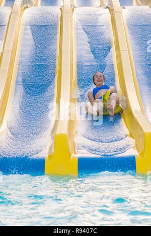 Fun in the sun-pretty girl in bikini descend en chute d'eau de piscine. Belle fille à cheval d'une glissade d'eau. femme heureuse qui descend à la ru Banque D'Images