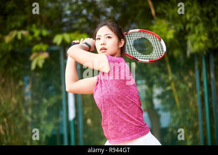 Young Asian woman tennis player hitting ball avec forehand Banque D'Images