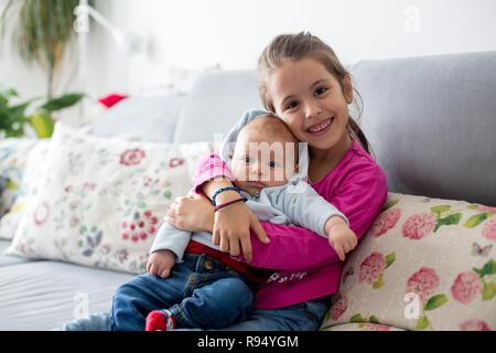 Sweet sister hugging son jeune frère bébé à la maison Banque D'Images
