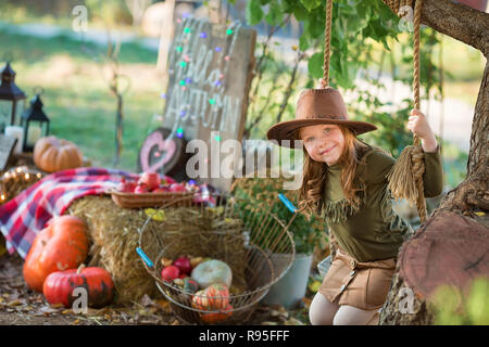 Funny Girl enfant kid en costume orange halloween jouer piscine avec jack spooky pumpkins avec visages effrayants sitting on swing West Highland White terri Banque D'Images