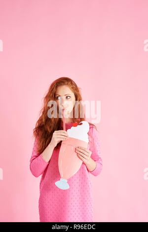 Woman drinking milk-shake au studio shot Banque D'Images