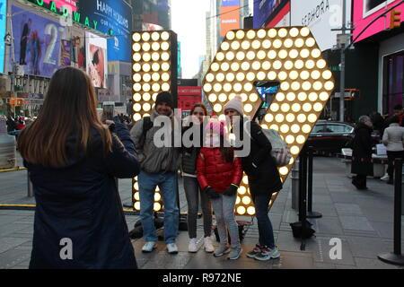 New York, USA. Dec 19, 2018. Visiteurs en ligne Times Square en face de l'allumé 19 pour une photo. Dans les prochains jours, les chiffres sont d'être hissé à bord, ainsi qu'une tour afin de former la nouvelle année 2019 avec la '2' et '0'. (Dpa ''19': Times Square se prépare pour Silvesterspektakel' à partir de 20.12.2018) Crédit: Christina Horsten/dpa/Alamy Live News Banque D'Images