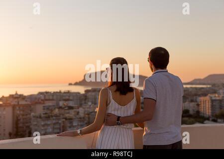 Jeune couple en tenue d'été bénéficiant d'une vue sur la ville depuis le toit-terrasse à Alanya en Turquie. Banque D'Images