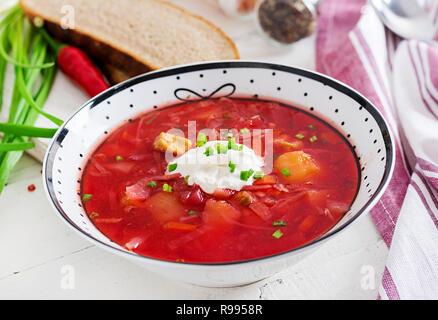 Bortsch Russe Ukrainien traditionnel avec des haricots blancs sur le bol. Soupe de betteraves. Assiette de soupe de racine de betterave rouge sur tableau blanc le bortsch. Ukra traditionnels Banque D'Images