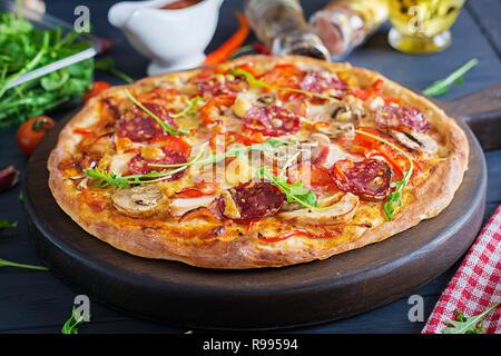 Pizza italien frais avec filet de poulet, champignons, jambon, salami, fromage, tomates sur un fond noir. Cuisine italienne. Banque D'Images