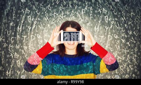 Happy young woman holding smartphone fermer les yeux pour s'amuser tout en différentes lettres sont voler autour de sa tête. Puissance hypnotique de la littérature et de l'edu Banque D'Images