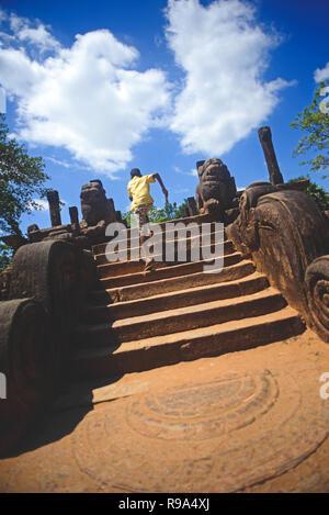 Garçon courir vers le haut des escaliers à, d'une salle d'audience dans la ville antique Polonnaruwa, Sri Lanka Banque D'Images