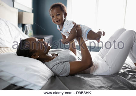 Playful mother holding baby son on bed Banque D'Images