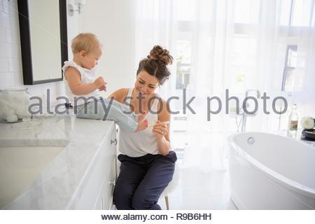 Mère de chatouiller les orteils de fille de bébé dans la salle de bains Banque D'Images