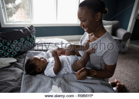 Happy mother and baby son on bed Banque D'Images