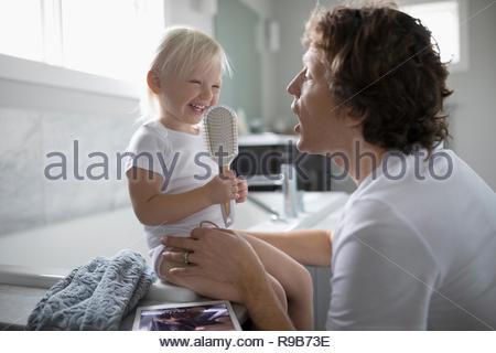 Père et fille enfant ludique avec brosse à cheveux dans la salle de bains Banque D'Images