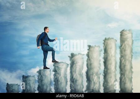 Homme confiant grimper jusqu'au sommet d'un graphe composé de nuages sur fond de ciel bleu. Pas de limites succès croissant concept, comme métaphore d'affaires continuer à Banque D'Images