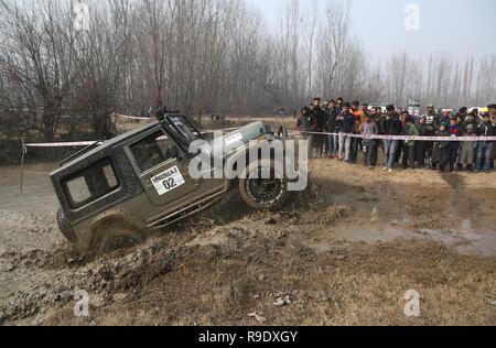 Srinagar, au Cachemire sous contrôle indien. Dec 23, 2018. Les gens regardent une jeep en action lors d'un 4x4 de boue autocross event en banlieue de la ville de Srinagar, au Cachemire sous contrôle indien, le 23 décembre 2018. La boue 4x4 autocross événement était organisé par le Cachemire Off Road Club à stimuler motorsport dans la région. Credit: Javed Dar/Xinhua/Alamy Live News Banque D'Images