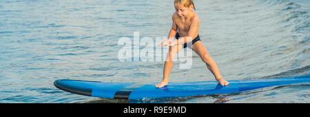 Petit garçon surf on tropical beach. Enfant sur planche de surf sur les vagues de l'océan. Sports d'eau Active pour les enfants. Piscine pour enfants avec surf. Leçon de surf pour les enfants BANNER, format long Banque D'Images