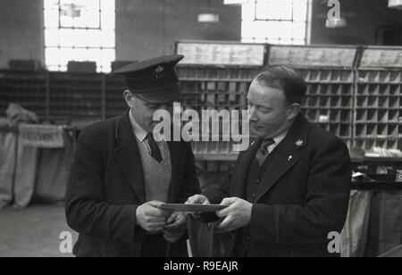 1948, photo montre deux Royal Mail en uniforme à l'intérieur du personnel d'un bureau de tri postal, England, UK, un postier avec cap debout avec son superviseur contrôle de l'adresse sur une lettre. Banque D'Images