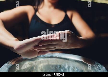 Cropped shot de jeunes femmes athlètes frappant des mains avec poudre de craie avant la formation de force. Banque D'Images