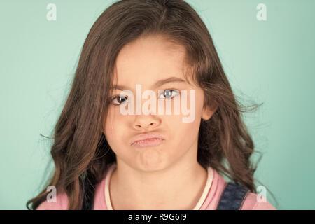Belle fille à la triste avec la moue des lèvres. Enfant mignon avec les cheveux longs. Banque D'Images