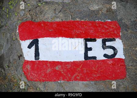 Chemin d'accès à longue distance européen E5 d'Oberstdorf (Allemagne) à Meran (Italie): Marque de piste rouge et blanc sur une pierre. Banque D'Images