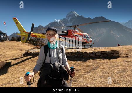 Le Népal, Trek au camp de base de l'Everest, Everest View Hotel, Trekker reposant à côté de l'héliport de Shree Airlines AS350 b3e Hélicoptère