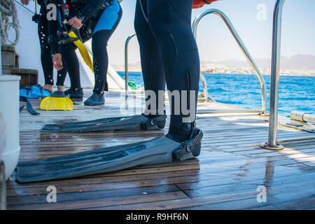 Vue rapprochée de jambes du plongeur en combinaison et palmes ( palmes). Les plongeurs se préparent à plonger. Des équipements de plongée. Plongée sous-marine Banque D'Images